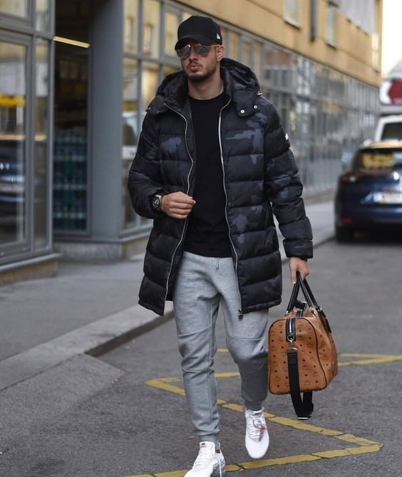 a sporty outfit with a black jumper, grey joggers, white trainers, a black printed puffer coat, a black cap