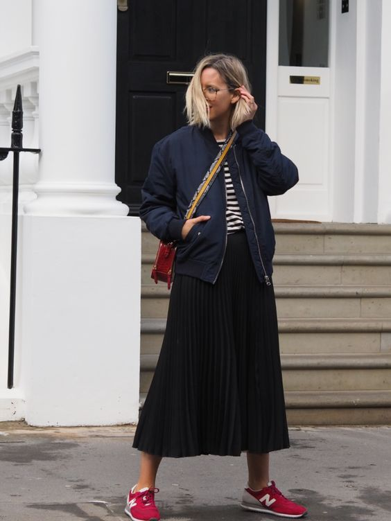a striped top, a black pleated midi, a navy bomber jacket, a red bag and trainers for a comfy everyday look