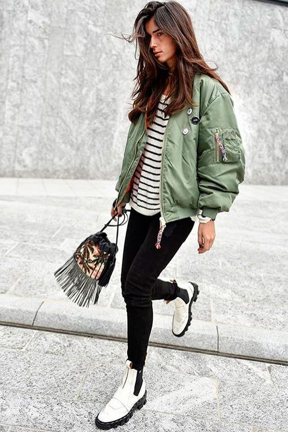 a striped top, black skinnies, white Chelsea boots on a platform, a green bomber jacket and a fringe bag