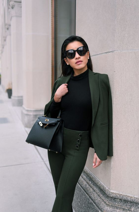 a stylish look with a black turtleneck, a dark green pantsuit with buttons, a black bag and touches of gold