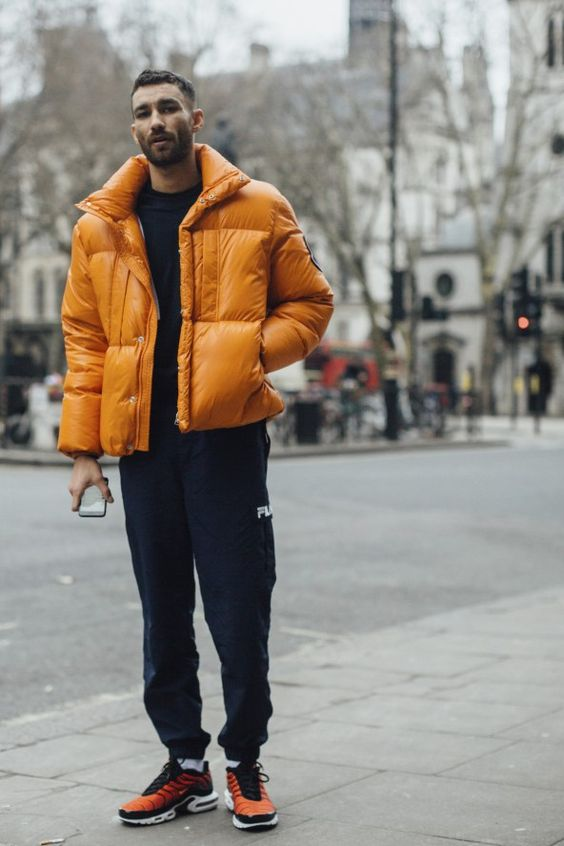 a stylish sporty look with joggers, a black sweatshirt, orange trainers and a marigold puffer jacket