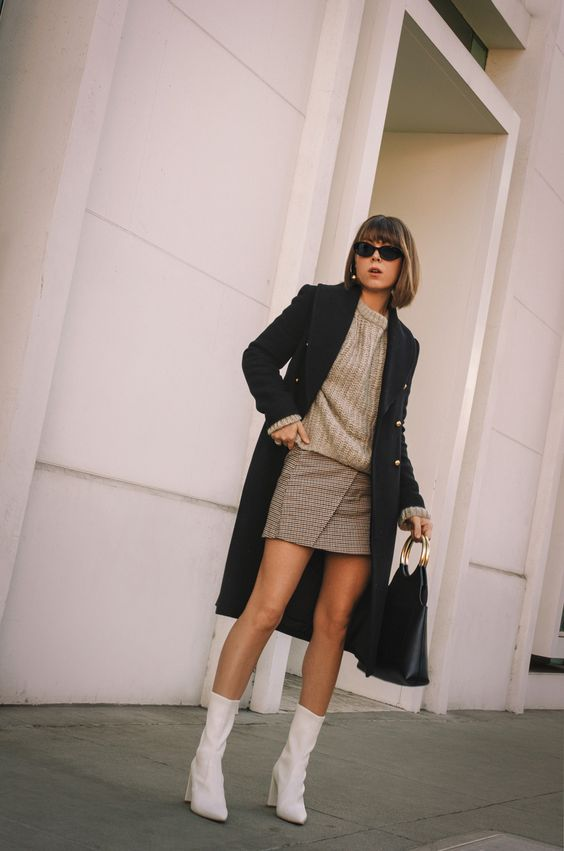 a stylish winter outfit with a grey chunky knit sweater, a beige wrap mini skirt, white boots, a black coat and a bag