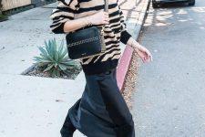 a tan and black zebra print sweater, a black midi skirt, black cowboy boots and a black studded bag