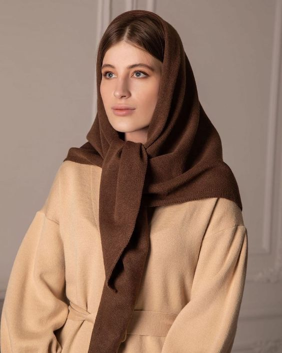 a tan coat plus a rown headscarf of wool make up a chic and non-traditional for winter combo