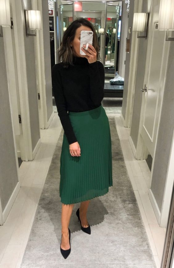 a timeless look with a black turtleneck, a green pleated midi skirt, black shoes compose a timeless look with a contrasting touch