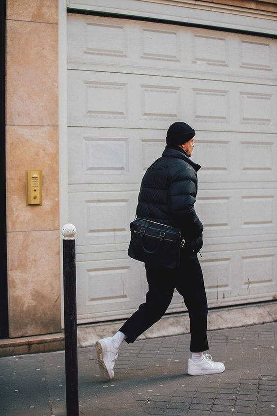 a total black look with a puffer jacket, black jeans, white trainers and socks, a beanie and a bag