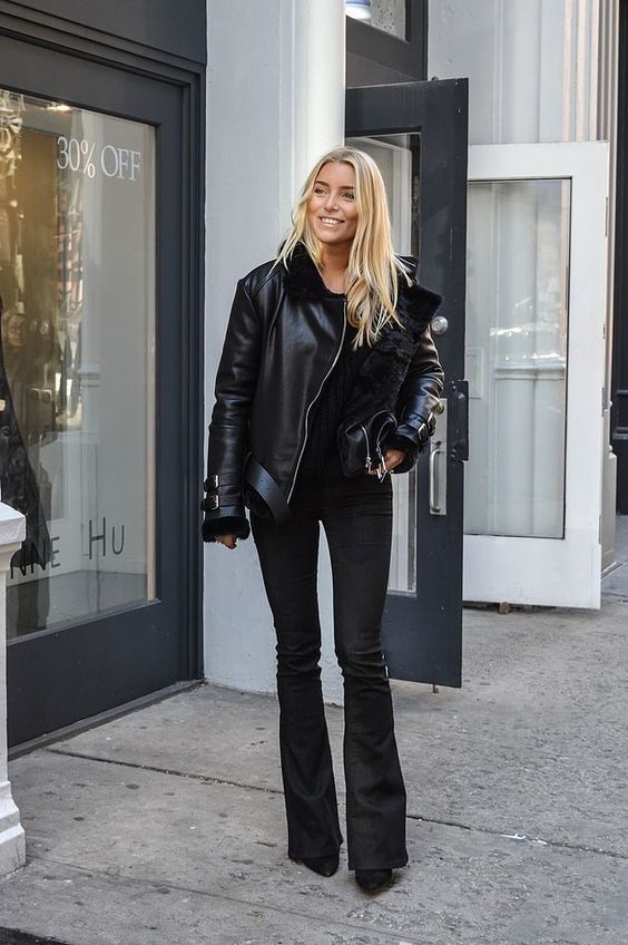 a total black look with a sweatshirt,, flare jeans, booties, a shearling jacket for winter