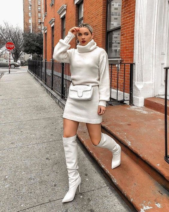 a total white outfit with a blouson sleeve sweater dress, a waist bag and knee high boots