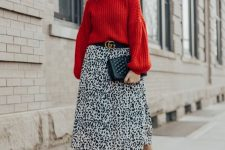 a trendy holiday look with a red puff sleeve chunky sweater, a leopard print skirt, black shoes and a black clutch