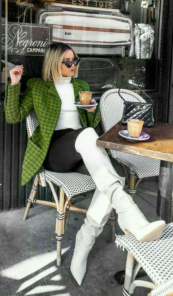 a trendy outfit with a white turtleneck and knee boots, black skinnies, a bold green printed blazer and a black bag