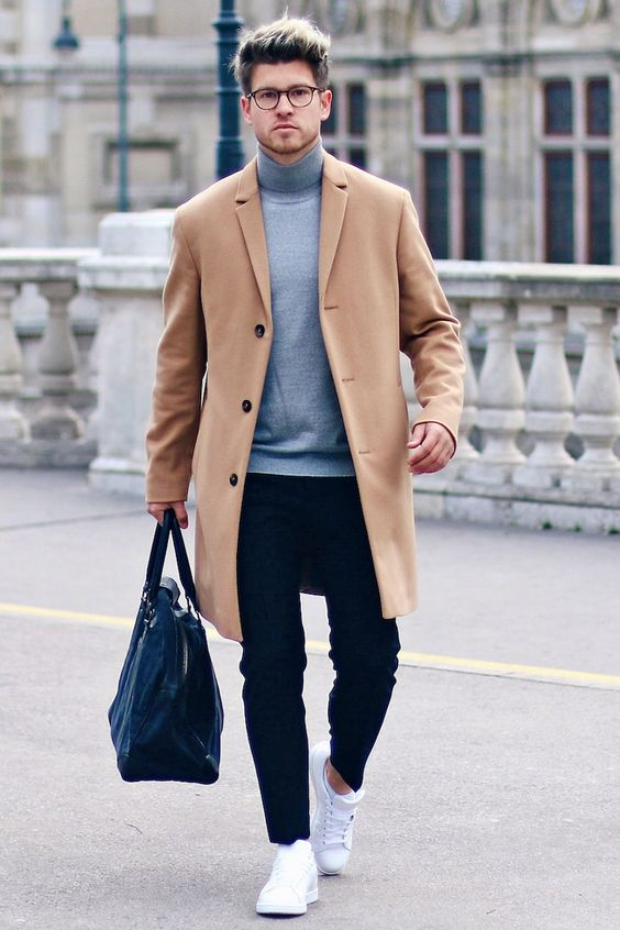 a very minimal work outfit with a grey turtleneck, black pants, white sneakers, a tan coat and a navy bag