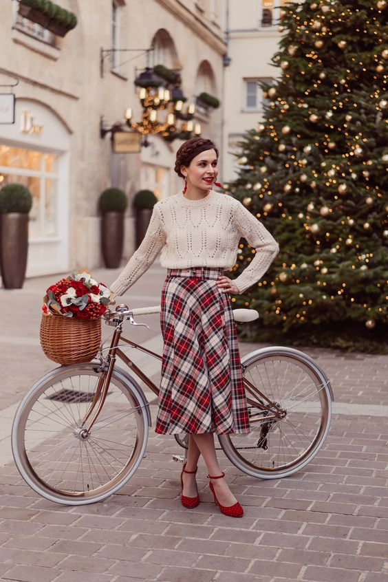 a vintage-inspired look with a white high neckline sweater, a plaid pleated midi, red shoes and a red lipstick