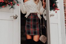 a white cable knit one shoulder sweater, a plaid mini skirt, black thigh boots and a leopard bag