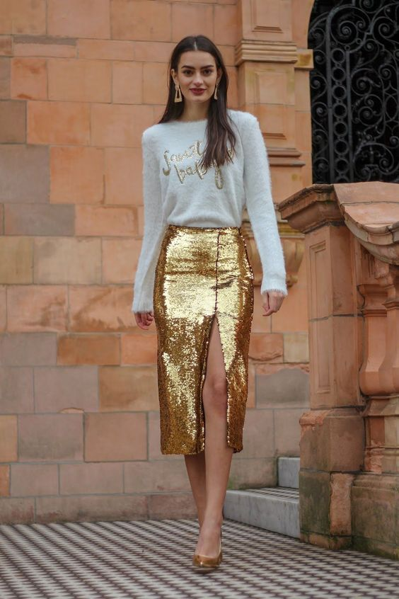 a white fuzzy sweater with embroidery, a gold sequin midi with a front slit and gold shoes for a glam look