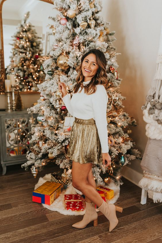 a white long sleeve top, a gold A-line mini skirt, tan booties for a chic and elegant Christmas look