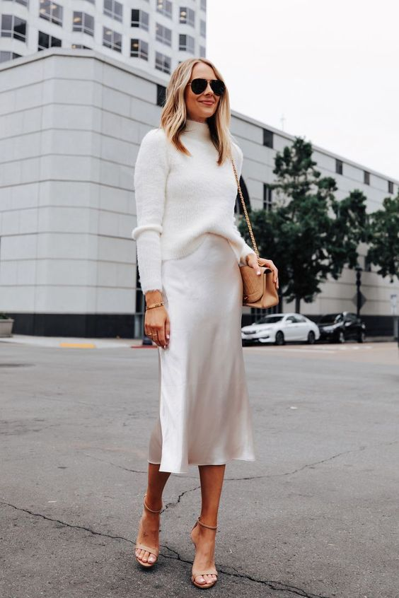 a white outfit with a turtleneck sweater, a slip midi skirt, nude shoes and a bag is very elegant