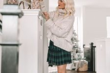 a white oversized braided sweater, a green tartan pleated mini skirt, nude booties for a cozy and chic look
