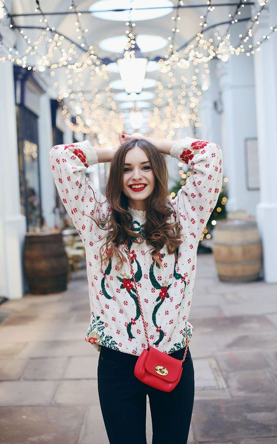 a white printed and holiday-themed sweater, black jeans, a red bag and a red lipstick for a super cool look