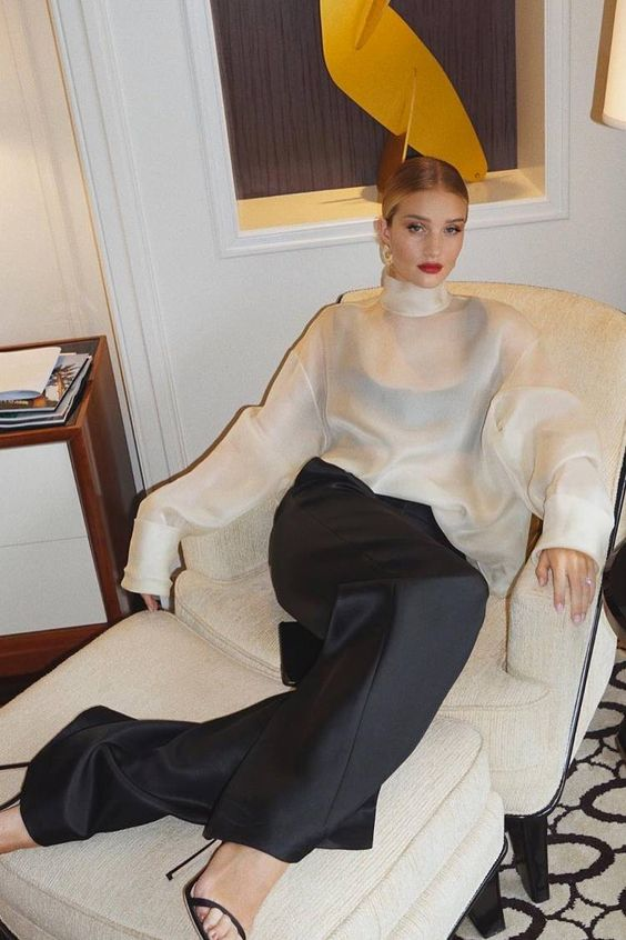 a white sheer oversized blouse with a black bra under it, black paalazzo pants, black heels and a red lip