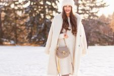a white sweater dress, grey suede boots, a grey bag, a white faux fur coat and a fur hat