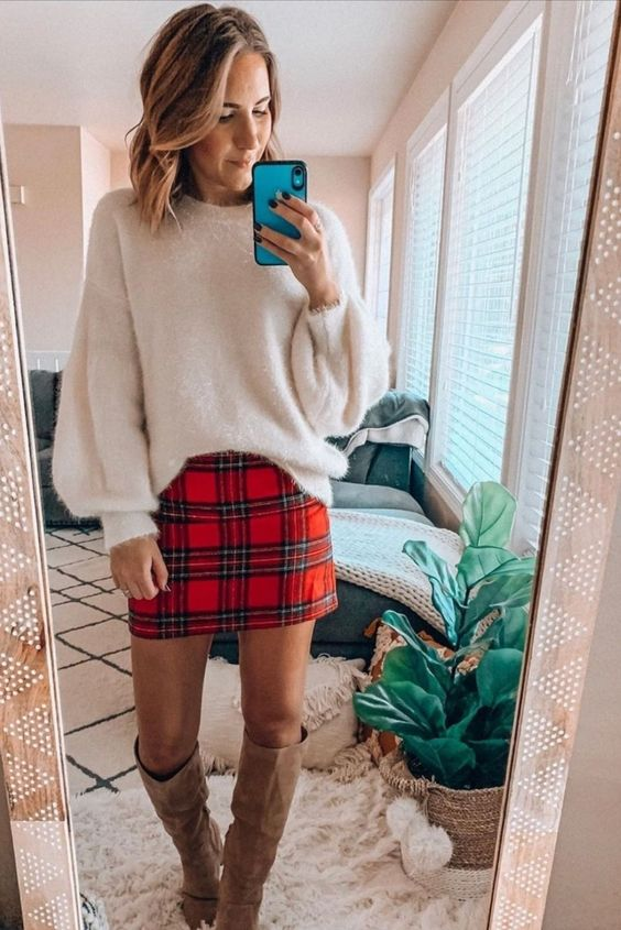 a white sweater with a shiny touch and puff sleeves, a red plaid mini skirt, tan knee boots for a chic look