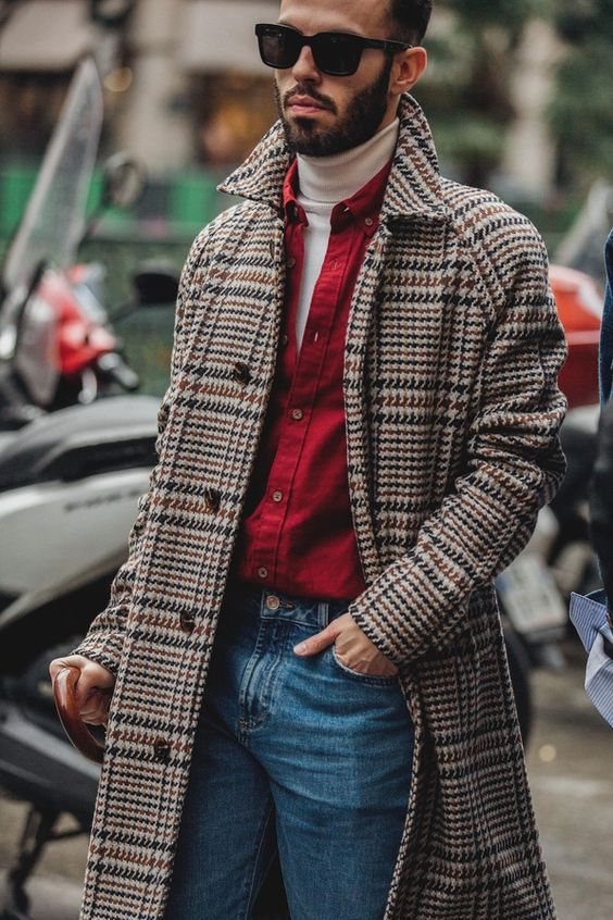 a white turtleneck, a red shirt over it, blue jeans and a plaid warm midi coat for a retro inspired look