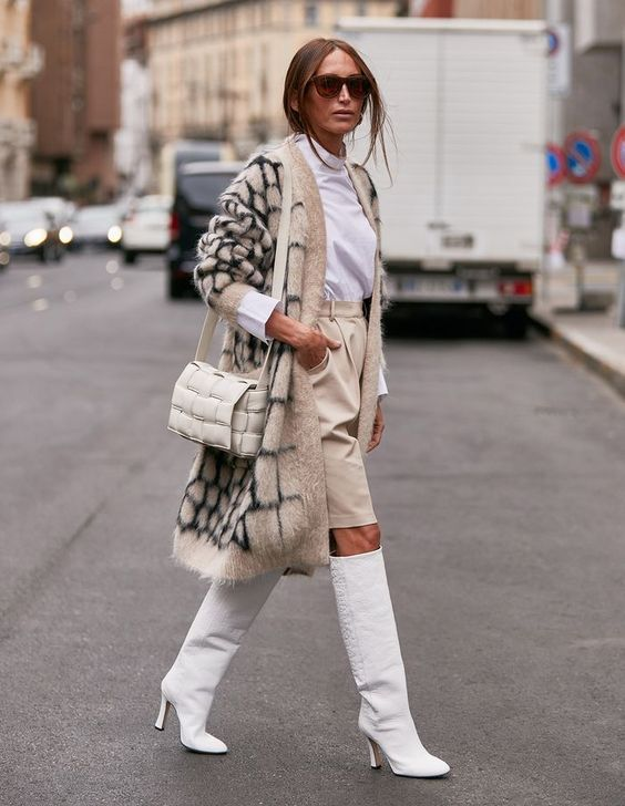 a white turtleneck, ivory shorts, white knee high boots, a printed fluffy cardigan, a creamy padded leather bag