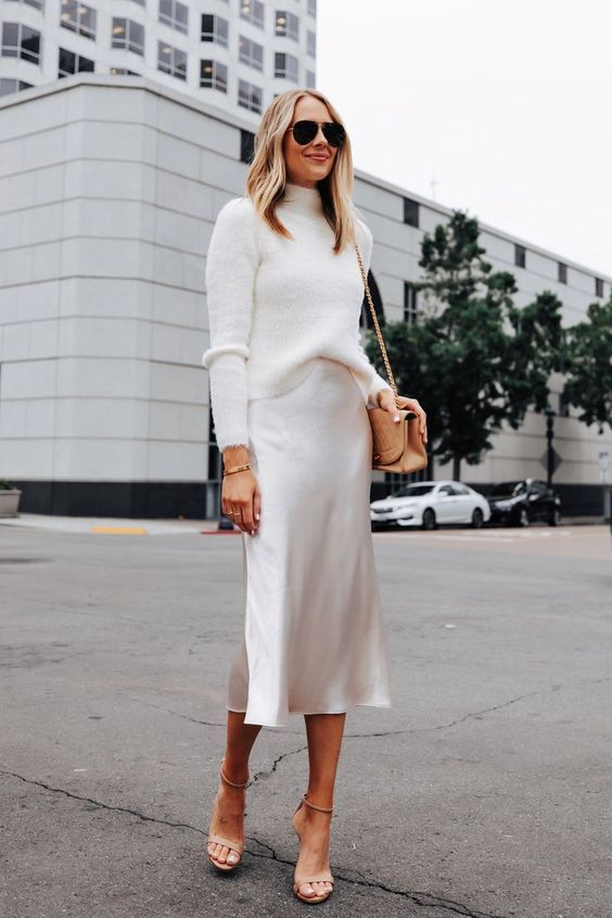 a white turtleneck sweater, a matching slip midi skirt, nude shoes and a tan bag for a luxurious touch