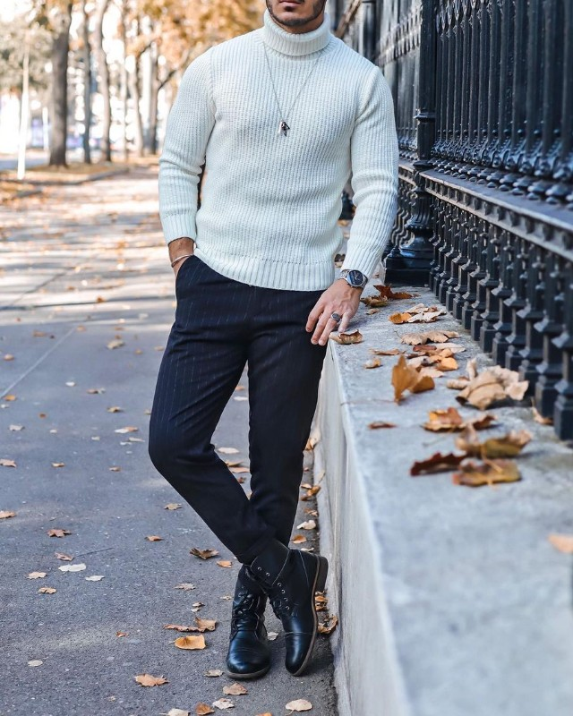 a white turtleneck sweater, black striped pants, black lace up boots and a necklace make up a chic monochromatic look
