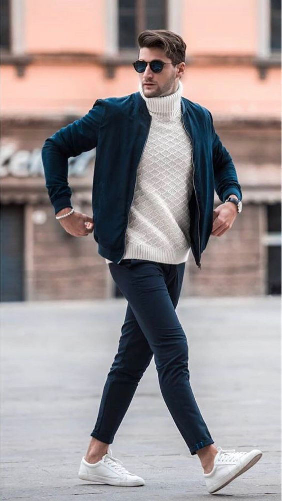 a white turtleneck sweater, navy trousers, white sneakers, a navy suede bomber jacket for a cool look