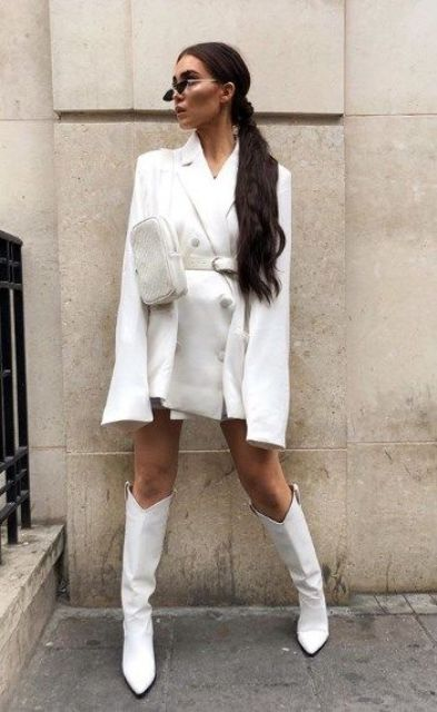 a wihte blazer dress, a white belt and a waist bag, white knee boots for a bold party look