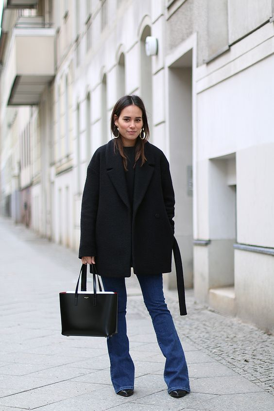a winter look with a black black sweater, blue flare jeans, black boots, a black coat, a black tote