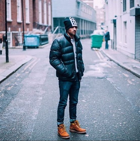 a winter outfit with blue jeans, a grey jumper, amber boots, a black puffer jacket and a black beanie