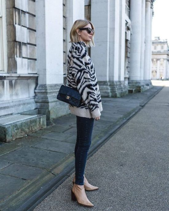 a zebra print sweater, navy skinnies, tan booties and a black bag for a bold and trendy winter outfit