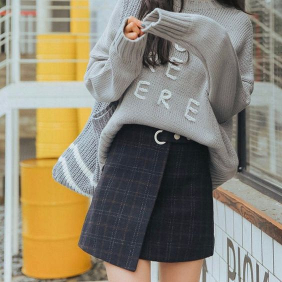 an embroidered light grey oversized sweater, a black tartan wrap mini skirt, a grey woven tote with stripes for winter