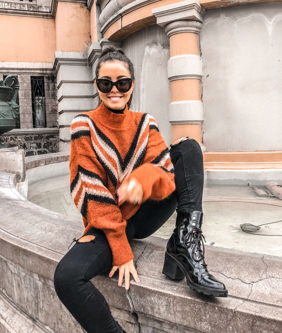 an orange geometric turtleneck sweater, black ripped jeans, black boots for a bold and pretty outfit