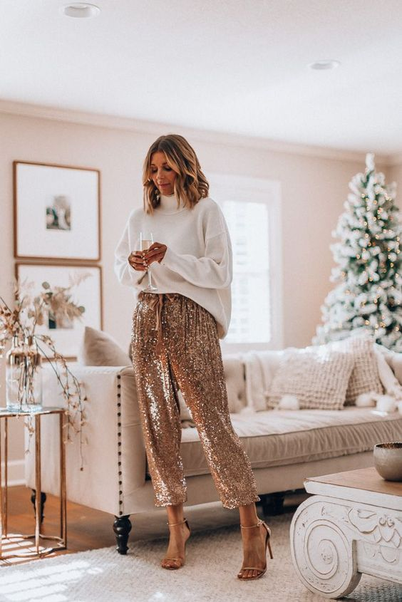 an oversized white sweatshirt, gold equin pants with a bow for a simple and effortless look