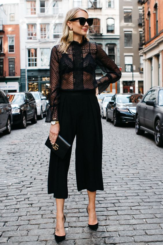 black culottes, a black polka dot blouse over a black bra, black heels, a clutch and statement earrings