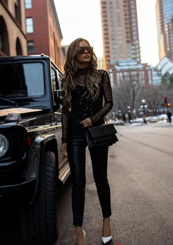 black leather pants, a black strap top and a sheer embellished top over it, a black bag and white shoes
