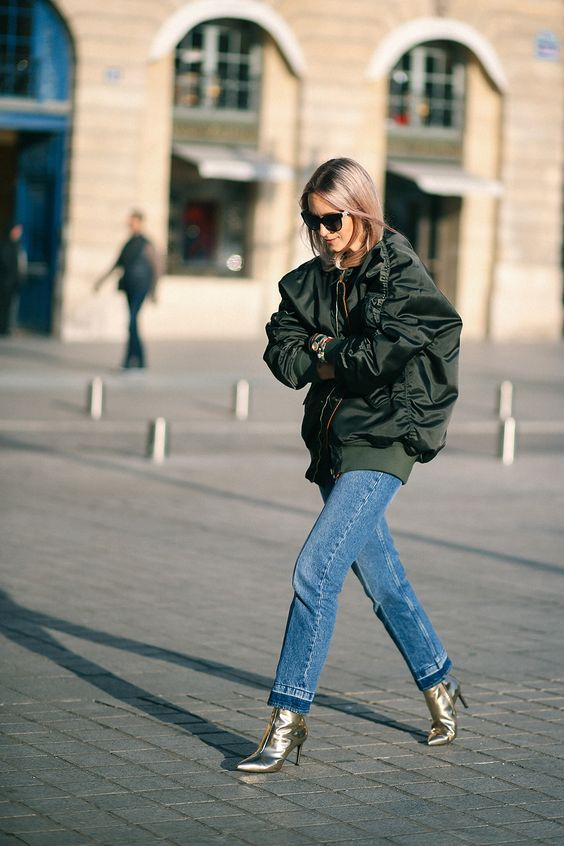 blue jeans, metallic boots, an oversized black bomber – add a sweater and a cozy look is ready
