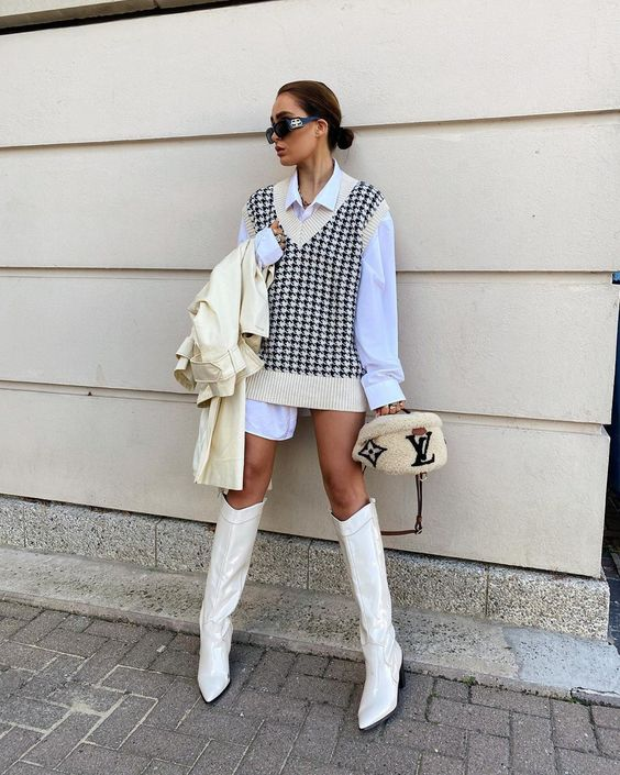 en edgy look with an oversized white shirt, an oversized knit vest, white boots, a white leather trench and a fur bag