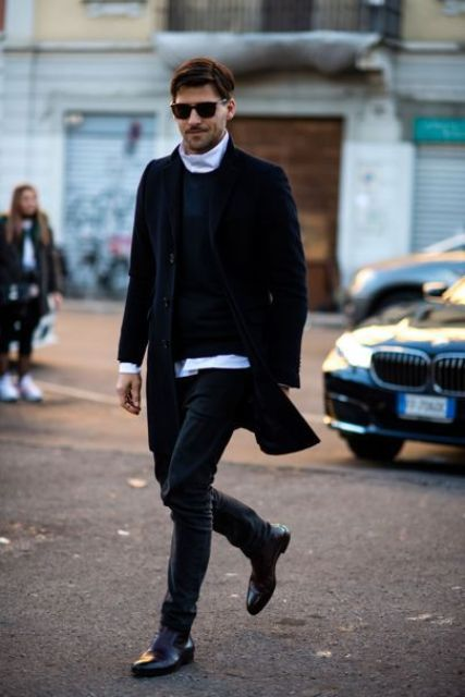 graphite grey jeans, a white turtleneck and a navy jumper, burgundy boots and a black coat for a stylish layered look