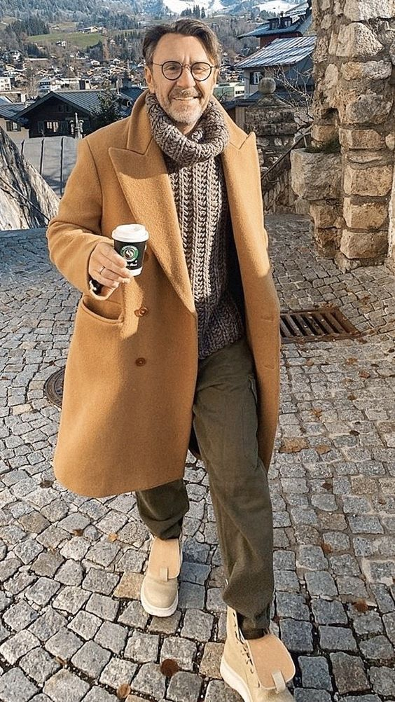 green pants, a grey chunky knit oversized sweater, tan boots, a tan coat compose a relaxed look