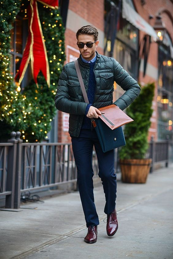 navy pants, a navy jumper over a blue shirt, a green puffer jacket, burgundy shoes and a twon tone bag for a chic work look