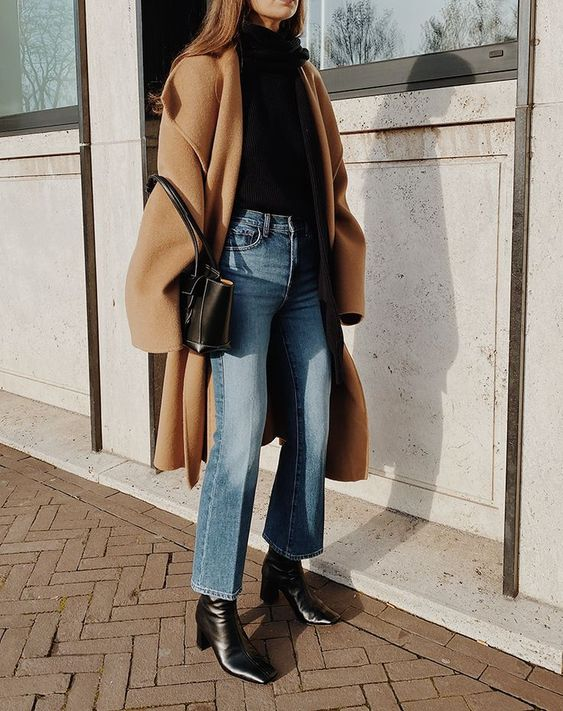 winter look with a black turtleneck sweater, blue flare jeans, square toe boots, a tan coat and a black bag