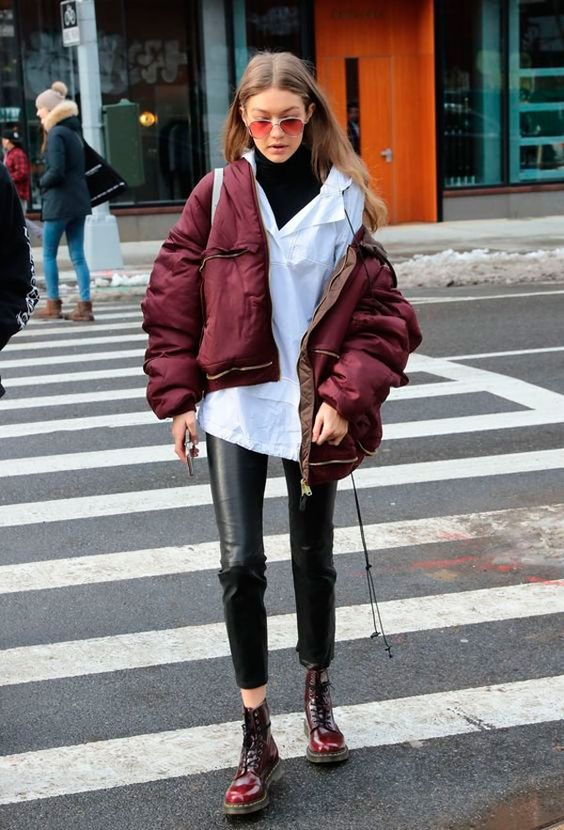 Gigi Hadid wearing a black turtleneck, a white shirt, black leather pants, burgundy boots and a puff jacket for a cozy look