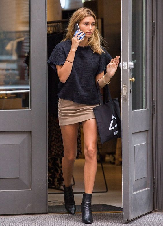 Hailey Baldwin wearing an oversized black sweatshirt, a tan mini skirt, black boots and a black tote