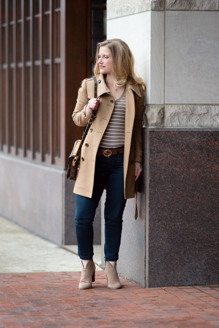 With beige coat, bag, navy blue jeans and gray boots
