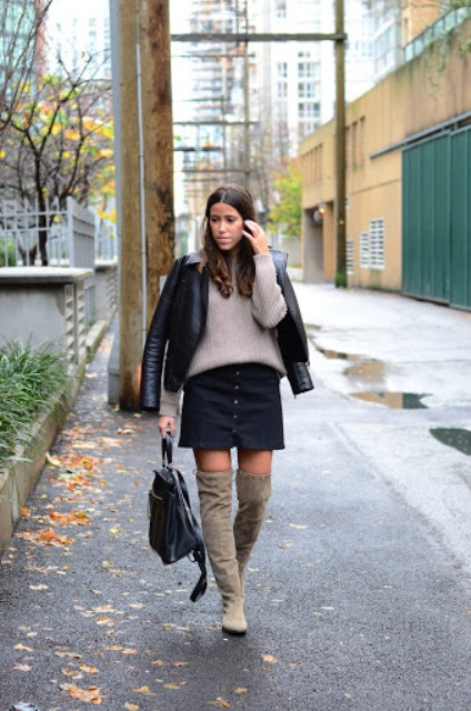 With beige sweater, black leather jacket, skirt and black backpack