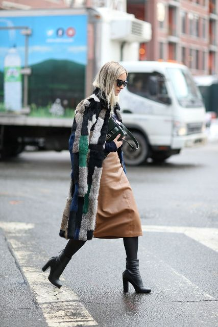 With black shirt, black bag, brown leather midi skirt and ankle boots